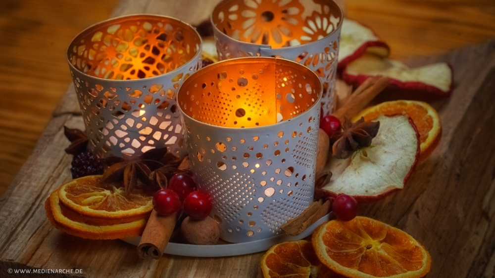 Drei Teelichthalter mit brennenden Kerzen warm erleuchtet inmitten von getrockneten Apfel- und Orangenscheiben, Sternanis, Zimtstanden, Beeren und Nüssen.