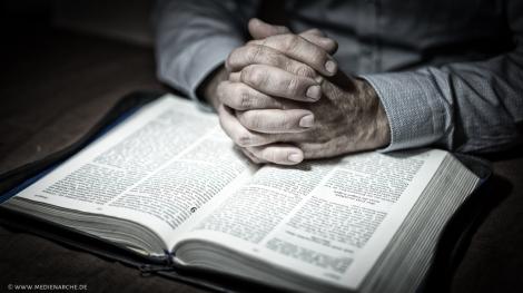 Zum Gebet gefaltete Hände auf einer Bibel. Inspiriert durch Kolosser 2,7: Seid in ihm verwurzelt und baut euer Leben ganz auf ihn. Bleibt im Glauben fest und lasst euch nicht von dem abbringen, was euch gelehrt worden ist. Hört nicht auf zu danken für das, was Gott euch geschenkt hat (GNB).
