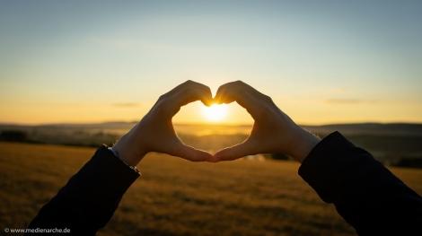 Zwei Hände, die ein Herz formen. Durch das Herz sieht man die aufgehende Sonne.