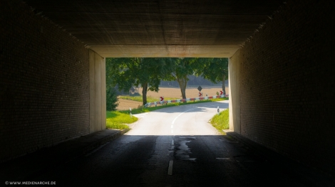 Blick aus einem Tunnel heraus auf eine sonnige Landschaft.
