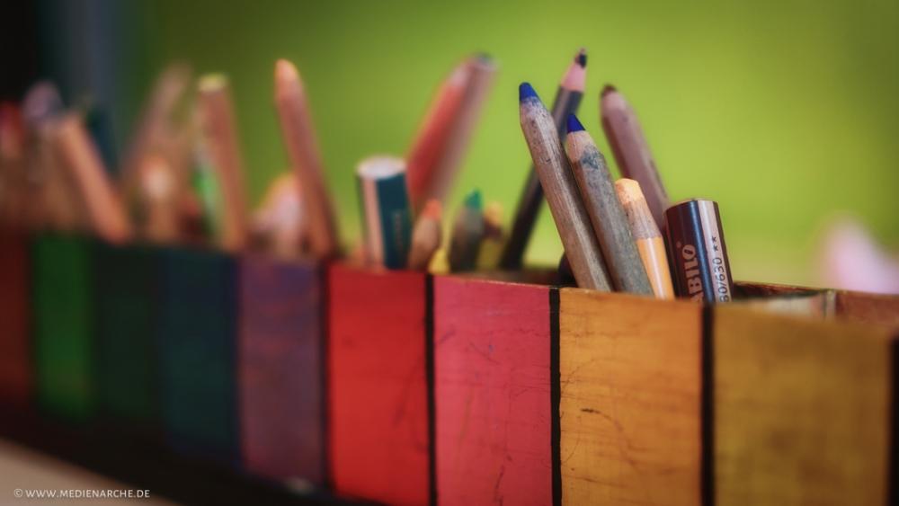 Nahaufnahme Malutensilien für Kinder in einer bunten Stiftebox.
